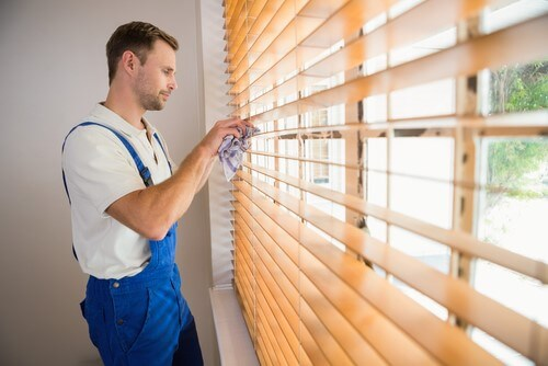 man in coveralls cleaning faux wood blinds with rag