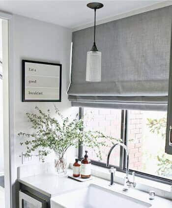 White kitchen sink with Roman Shades