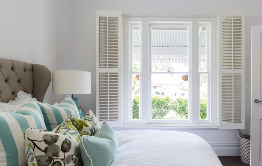 window in bedroom with white shutters